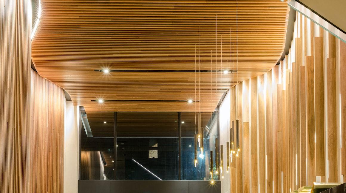 Aris linear grazer illuminates the custom timber battens in the main lobby entrance.