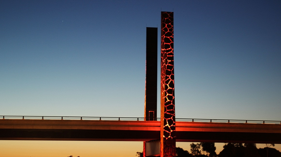 An installation of high-power linear luminaires inside the two mast features of the bridge. The luminaires create a glowing effect from inside the structure.