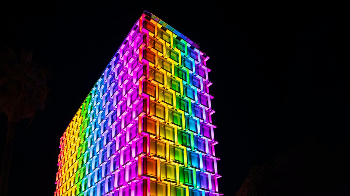 Latitude LED luminaire in application, installed on the facade on Council House in Perth. Colour changing feature is illustrated, the building is illuminated in rainbow colours.