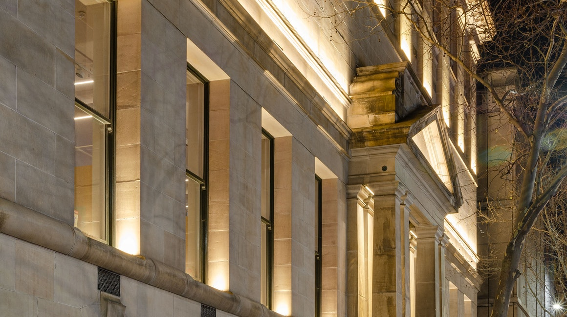 Max Mini IP LED luminaire in application. Discreet Max Mini IP linear floodlights highlight the façade at Melbourne State Library of Victoria. View on the facade from the side.