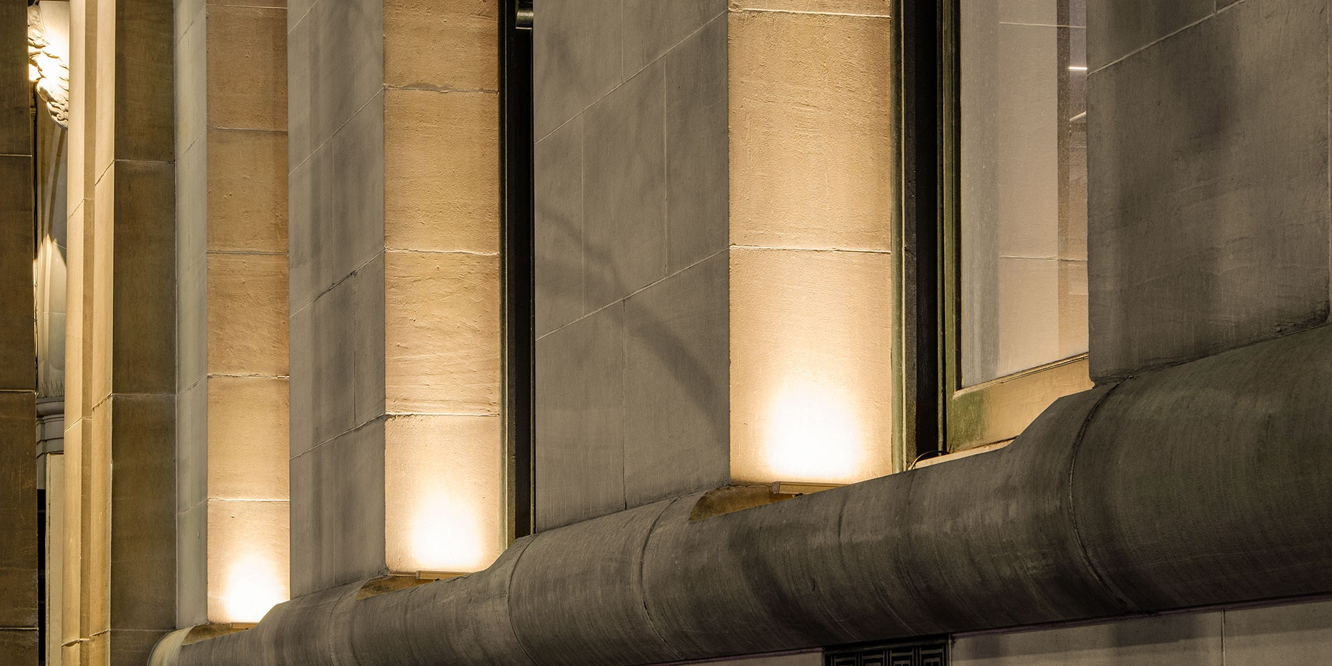 Max Mini IP LED luminaire in application. Discreet Max Mini IP linear floodlights highlight the façade at Melbourne State Library of Victoria. Close up on the columns.
