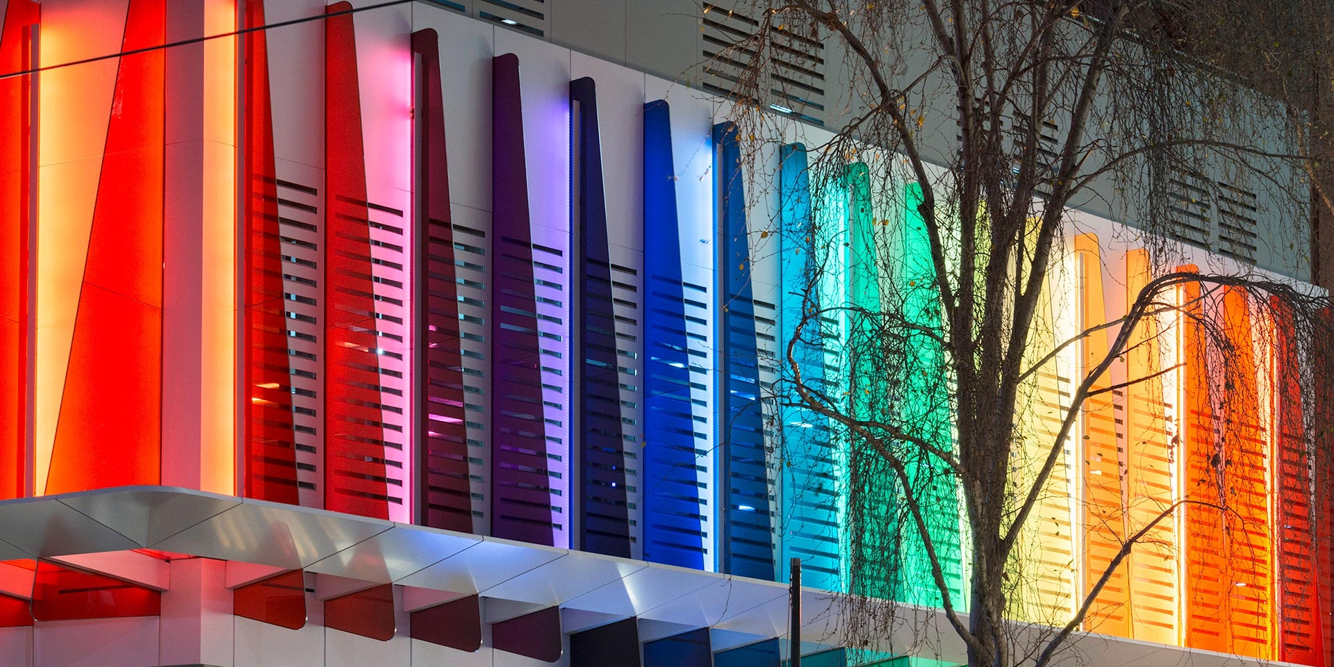 Maxis high-power linear flood light  in application, installed on the Strad Facade in Melbourne CBD. Every second coloured panel is illuminated by a Maxis high-power luminaire.