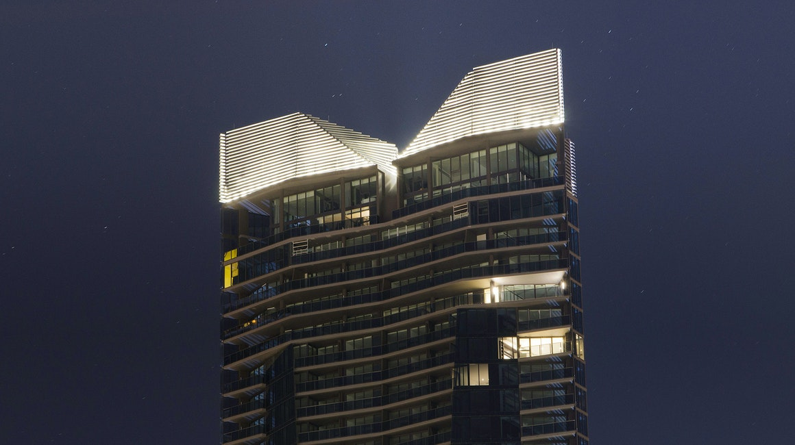 Maxis high-power linear flood light  in application, installed on Yarra Point (Tower 6). Maxis high-powered projector luminaires, complete with flare optics, are used to illuminate the architectural crown of the building.