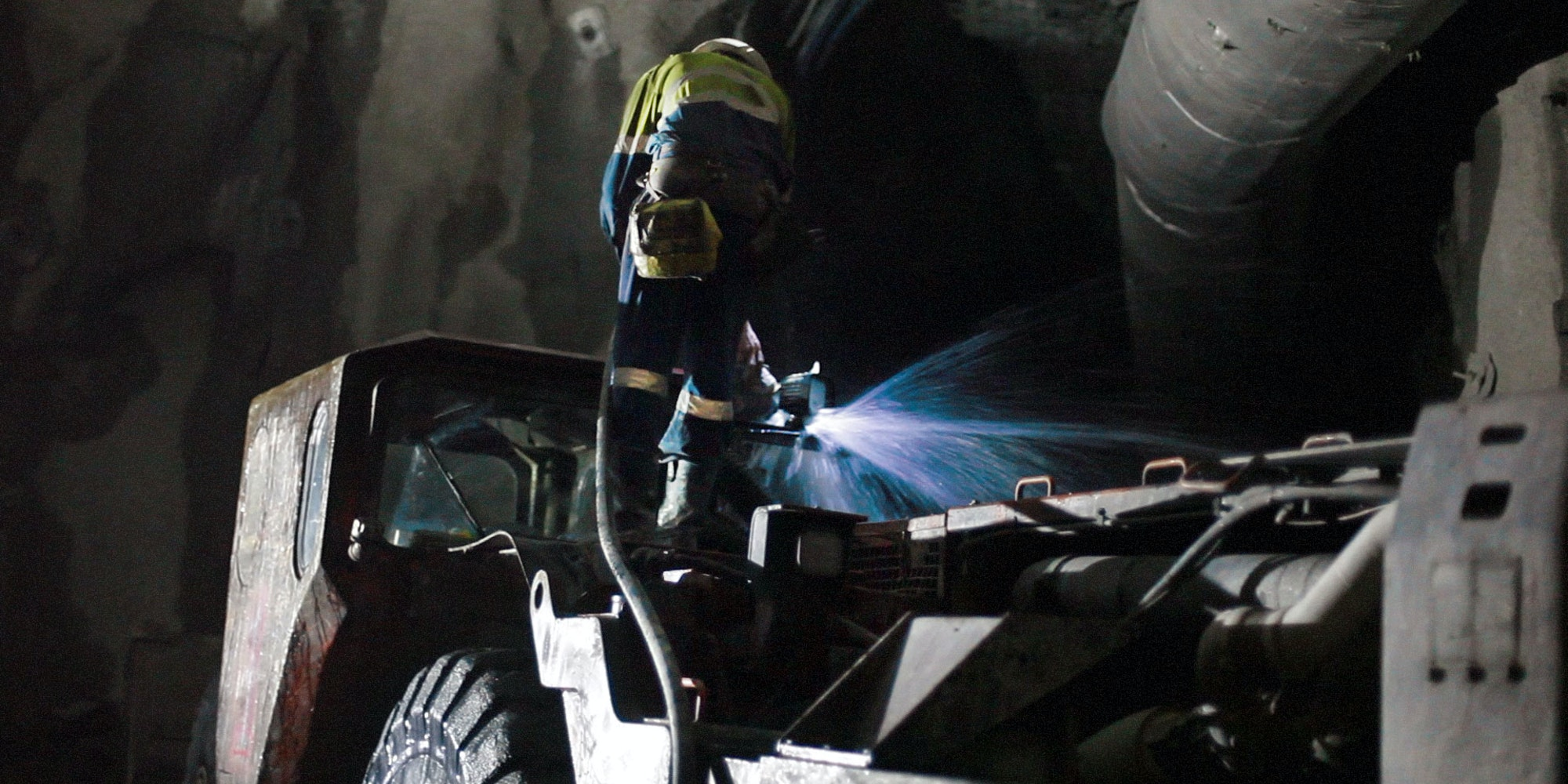 CPUG Series LED Work Light in application, installed on an underground excavator and high-pressure washed by a mine site personnel