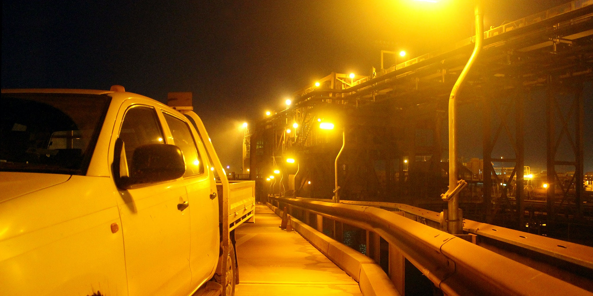 DLK2 LED Conveyor / Area Light in turtle-friendly amber colour temperature in application, installed in a bulk port in a fog